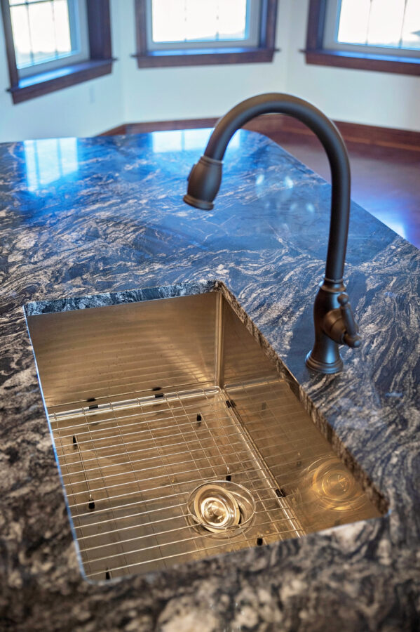 Granite kitchen countertop with drop-in single-bowl stainless steel sink.