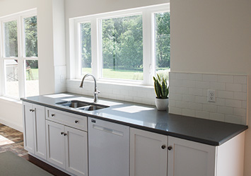 The large window in the kitchen behind the kitchen sink on the rear wall with white cabinets and walls and a quartz countertop
