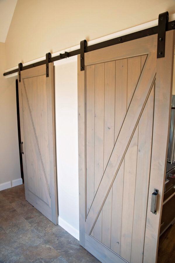 Vestibule area with 2 sliding barn doors closing off the kitchen & mud room
