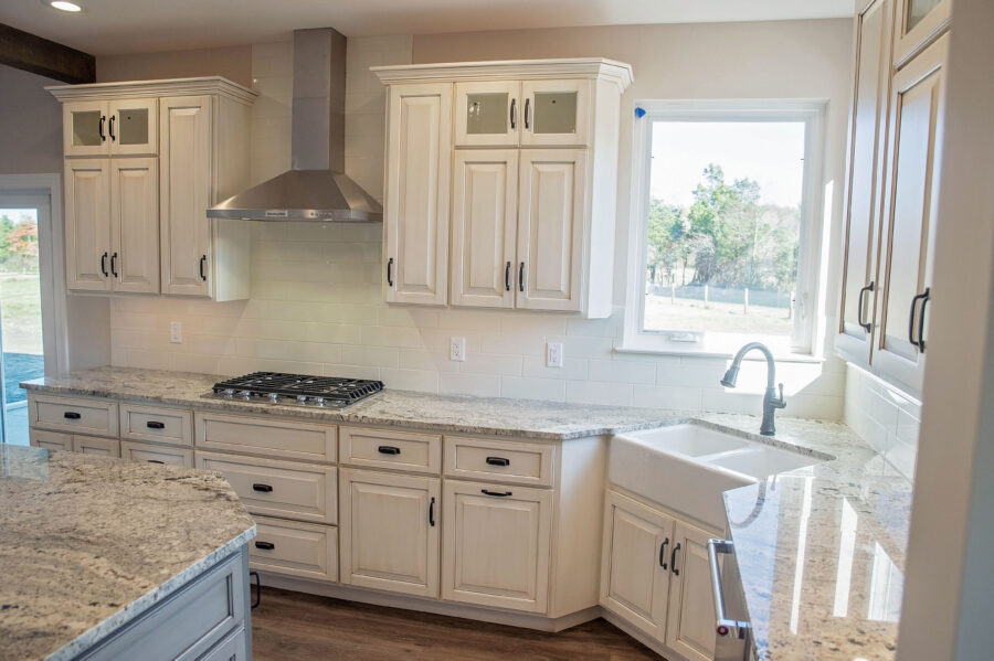 The kitchen with a Kohler double-bowl apron front sink and KitchenAid appliances with range hood vented to exterior.