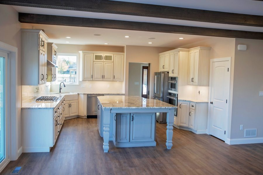 Custom built kitchen with custom white cabinetry and granite countertops and an island.