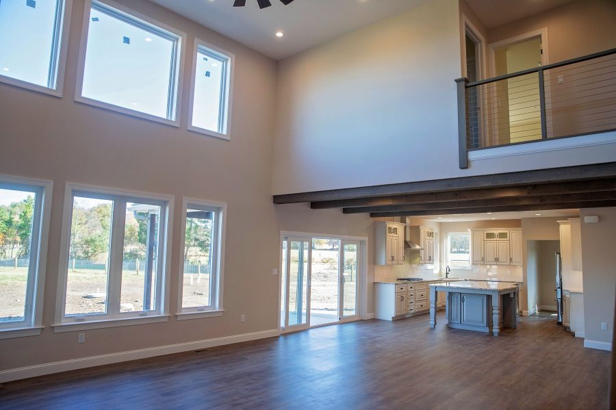 The Great Room looking into dining room area & kitchen with a 2-story great room with balcony above, faux wood beams at dining room area and luxury vinyl plank flooring throughout