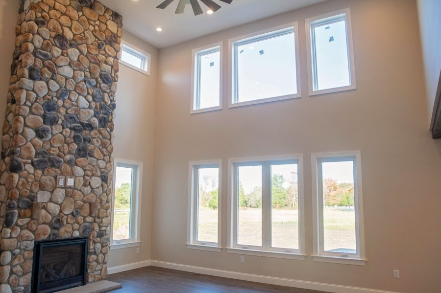 The 2-story great room with large windows and a gas fireplace with 2-story rubble stone surround