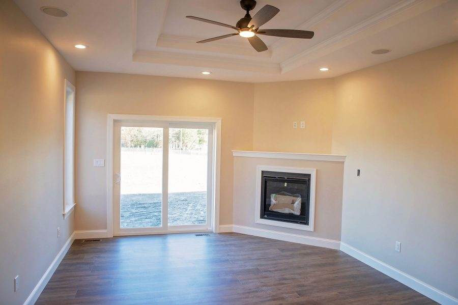 The Master bedroom with a 2-lite sliding patio door, a gas fireplace in corner and 2-step coffered ceilings with crown molding inside each section.