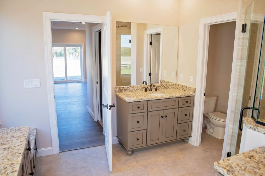 """The Master Bathroom wit Custom cabinetry, a """"His"""" vanity and luxury vinyl tile flooring"""