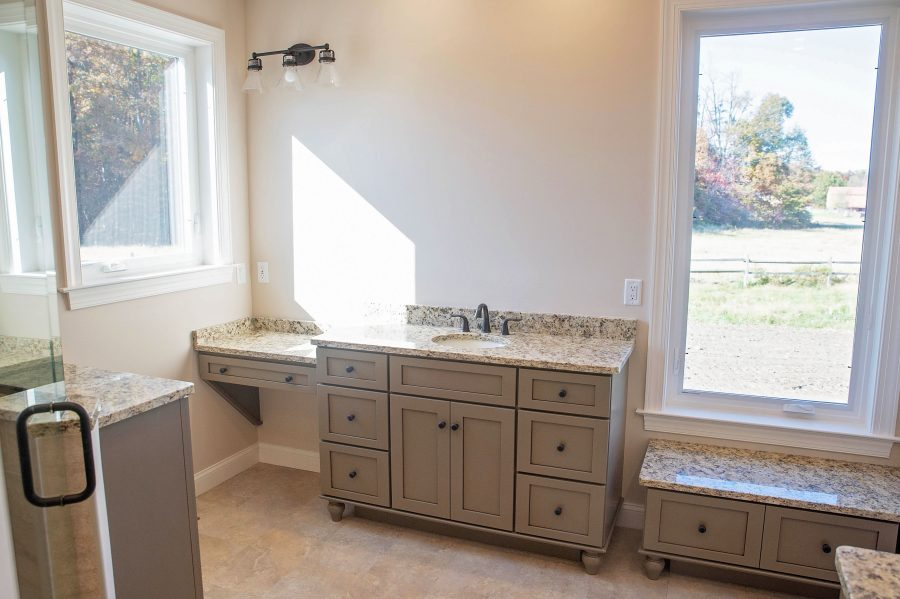 """The Master Bathroom with custom cabinetry, a """"Her"""" vanity with make-up vanity and bench and granite countertops with bright windows."""