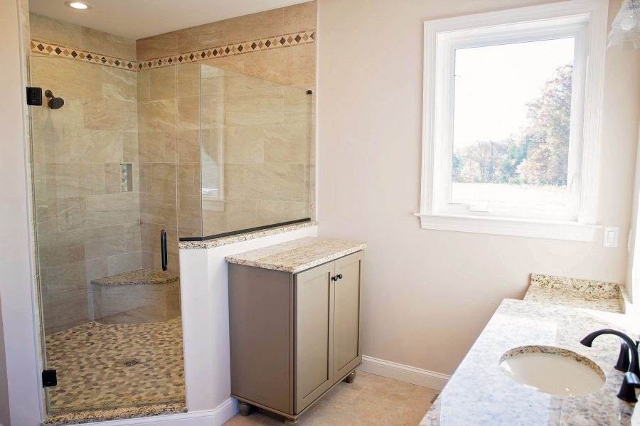 The custom built Master Bathroom with a custom designed tiled shower, cabinets, and a bright window.