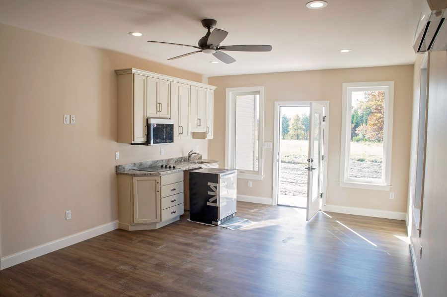 Custom built in-law suite with luxury vinyl plank flooring, custom cabinetry for a small kitchenette, granite countertops and a private entrance.