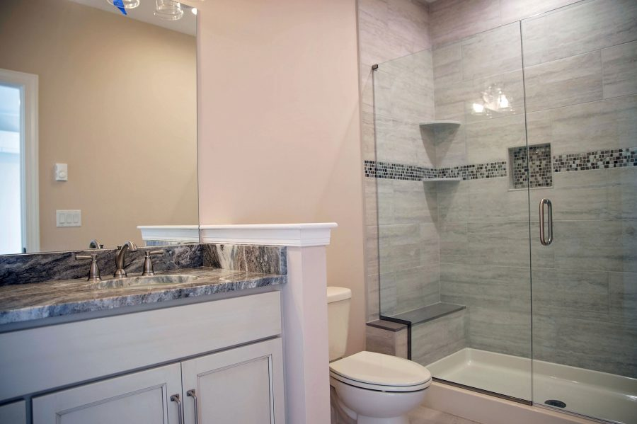 In-law Suite Bathroom with custom cabinetry, granite countertops and tiled shower walls with shower pan and a toilet.