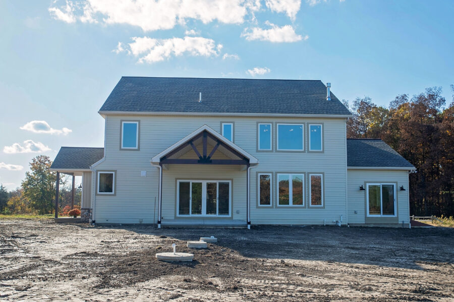 The right side of a custom home build in Montgomery County with a Viwinco 4-lite sliding patio door with timber frame truss