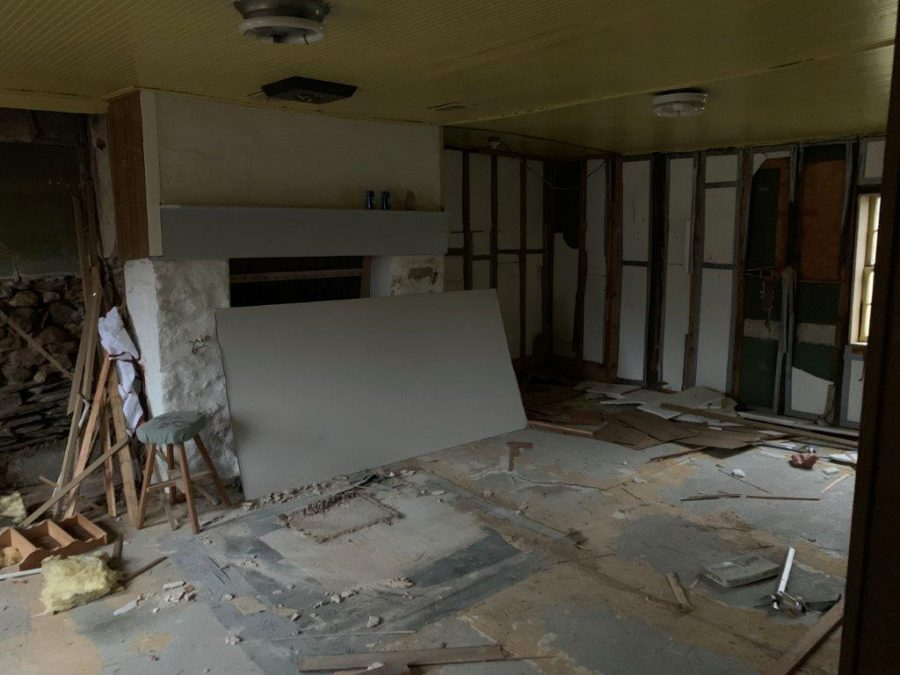 The demolished family room before the remodel with wood pieces everywhere and a torn up floor.
