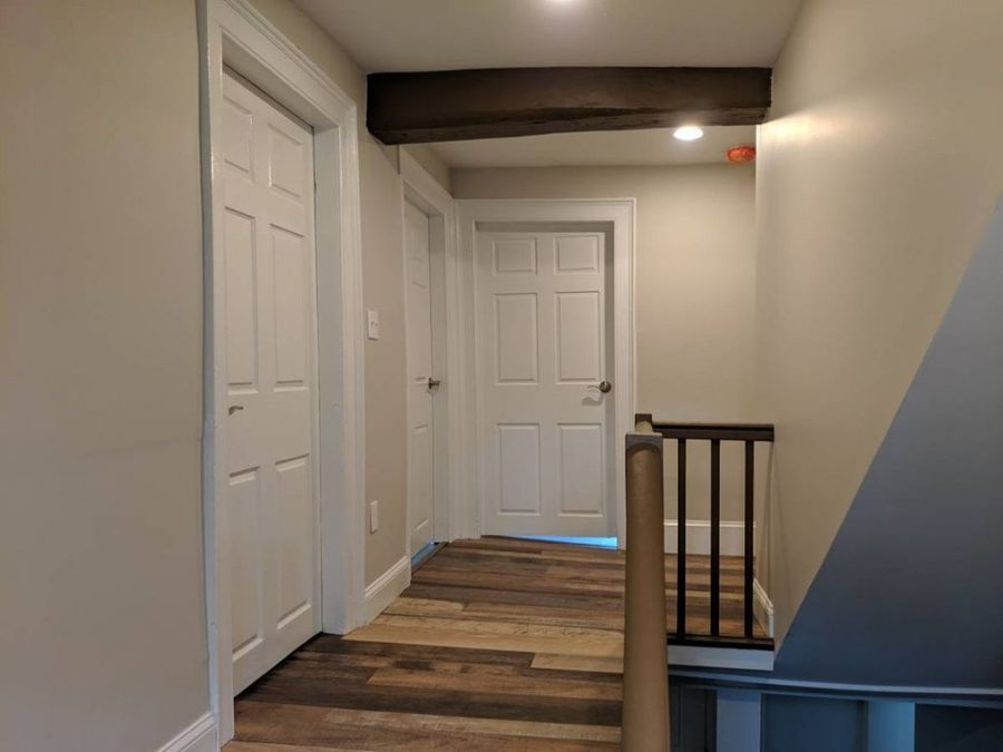 The stairwell and the hallway leading to the second floor fully remodeled with new drywall, electrical, luxury vinyl plank flooring.