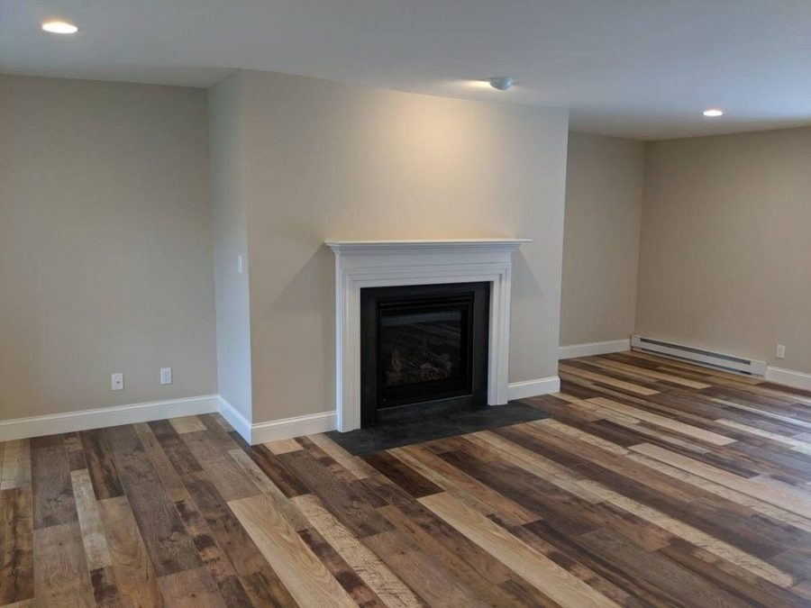 The family room after Corrado Custom Homes remodeled with a new gas fireplace, slate surrond and luxury vinyl plank flooring.