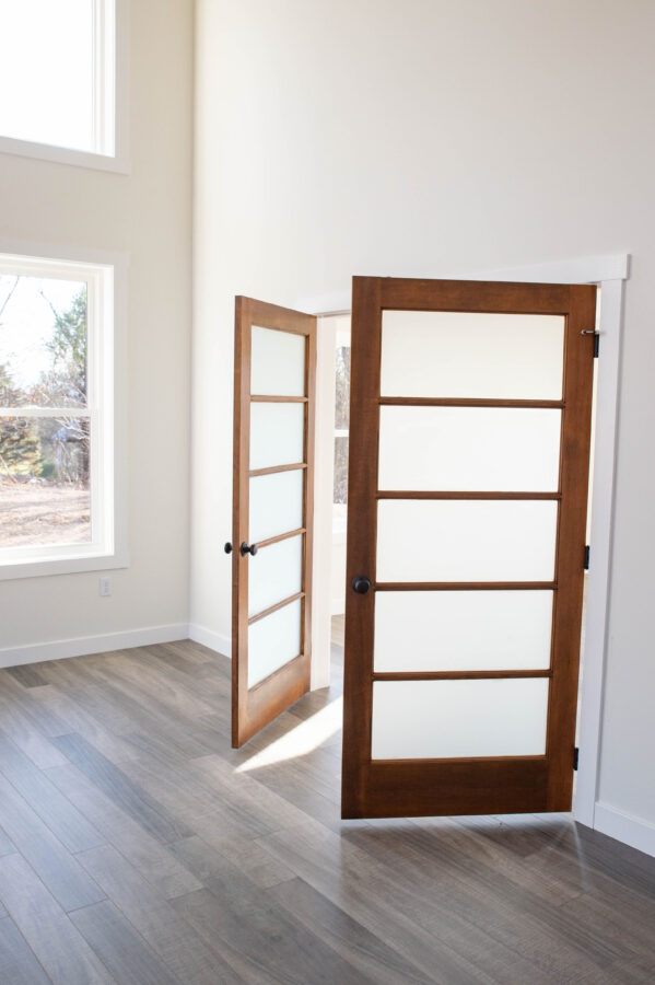 Wood den entry doors with frit glass hides the office and craft supplies from guests.