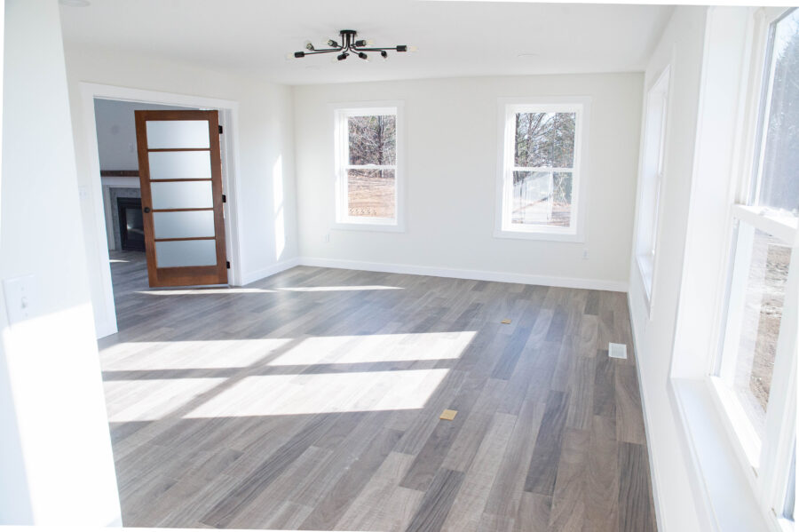Large den for office and craft room with hardwood floors and off-white walls