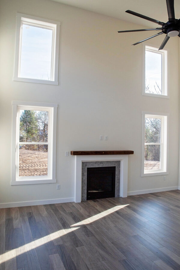 2 story great room with gas fireplace on one wall with four windows and off-white walls