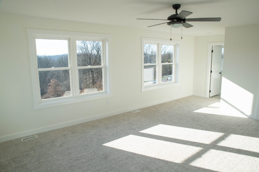 The Master Bedroom with off-white walls, a ceiling fan and light carpet.