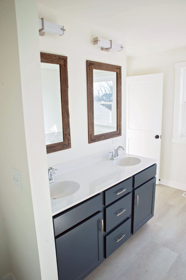 The Master Bathroom with a double bowl vanity with painted cabinetry, cultured marble countertops, and custom supplied mirrors.