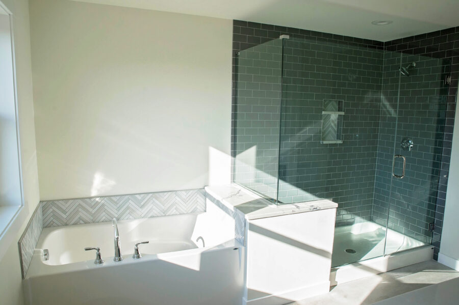 The Master Bathroom with a custom-designed tub and shower with herringbone pattern tile surrounds the tub and subway tile in the shower