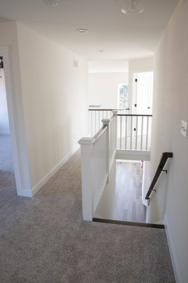 2nd Floor Hallway leading towards the master suite with white walls and a black railing going downstairs