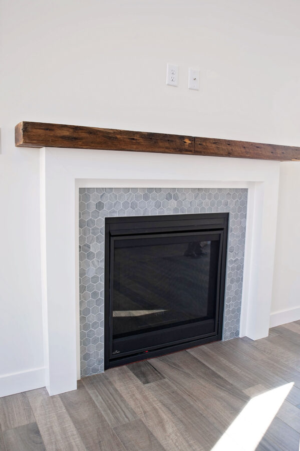 The homeowner's custom designed the fireplace surround with a fun, grey hexagon tile, white wood surround, and barn beam mantel.
