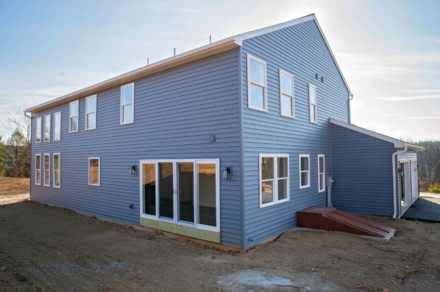 The rear of a Berks County custom-built home with slate blue siding and lots of windows.