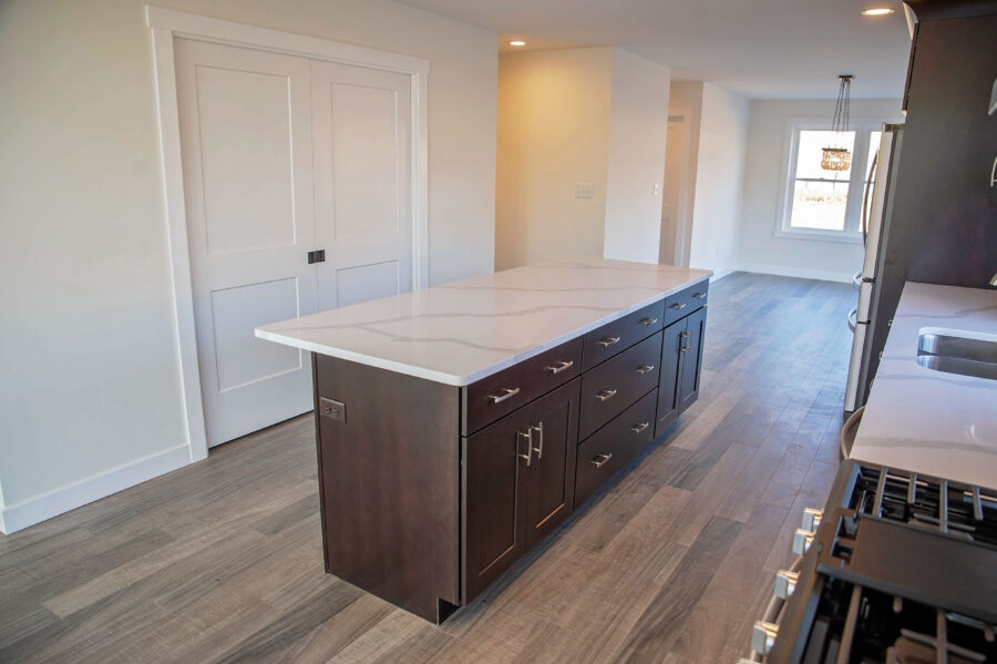 Oversized kitchen island to seat the whole family, with stained cabinetry and quartz countertops.