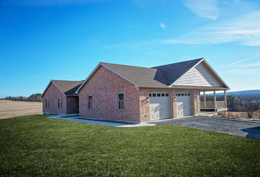 The right side of a custom-built brick home with a side Entry Garage with oversized 10' x 9' doors  and access to a rear, covered patio.
