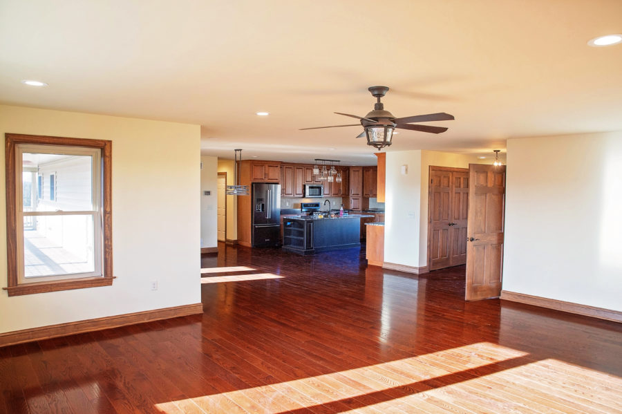 The Great Room with a rustic cieling fan, solid hardwood floors and stained casing and baseboards looking into the kitchen