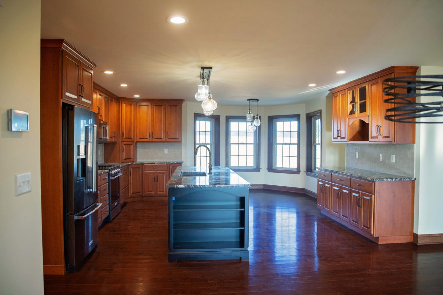 The main kitchen with customized two-toned maple stained wooden cabinetry and a painted, center kitchen island with a sink.