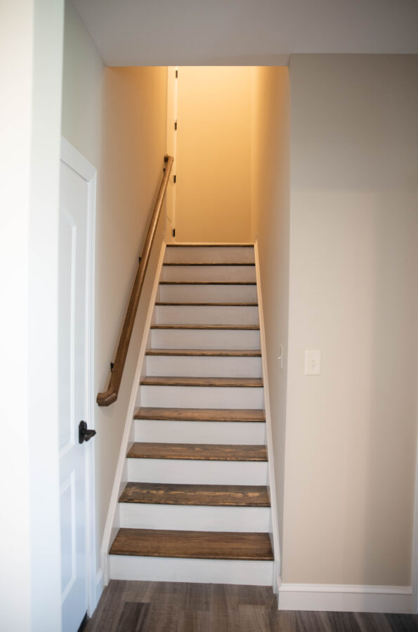 Oak-stained treads, painted riser stairs leading to finished bonus room above the garage.