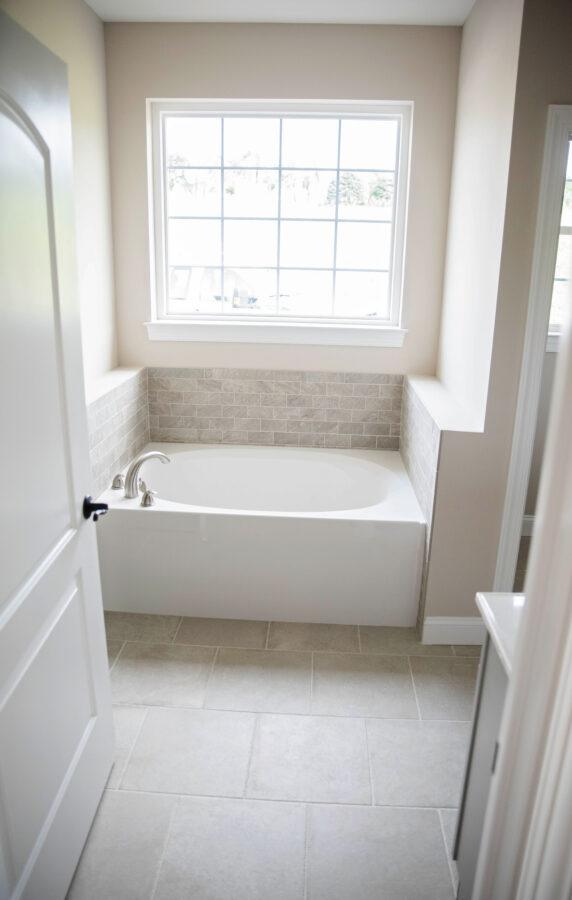 The Master Bathroom's white Slide-In soaking tub with a light beige-grey tiled backsplash under a large window