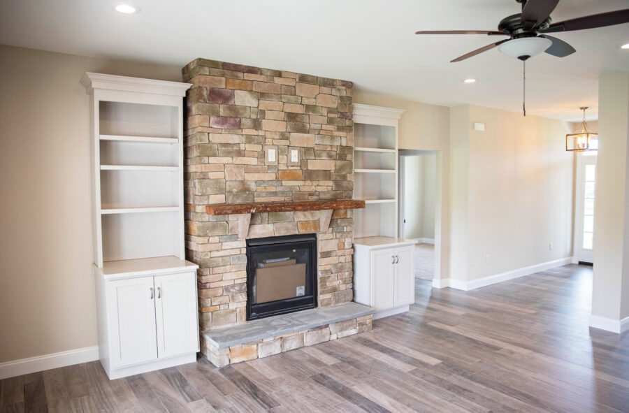 The Great room gas fireplace with full height stone surround, a raised hearth with 1-piece stone and a repurposed barn beam mantel.