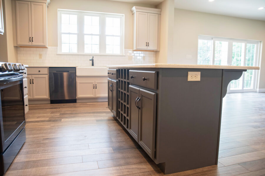 The kitchen sink wall with a farmhouse apron-front kitchen sink, with windows to bring in natural light and the dark grey island.