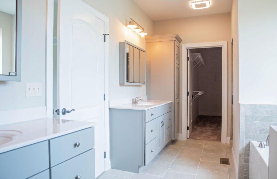 """The Master Bathroom with """"His"""" & """"Hers"""" vanities, light slate grey painted cabinetry, cultured marble countertops, and tri-view medicine cabinets."""