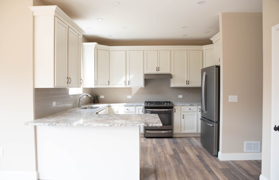 The kitchen with ample space on granite countertops with overhangs and white perimeter cabinetry and black appliances.
