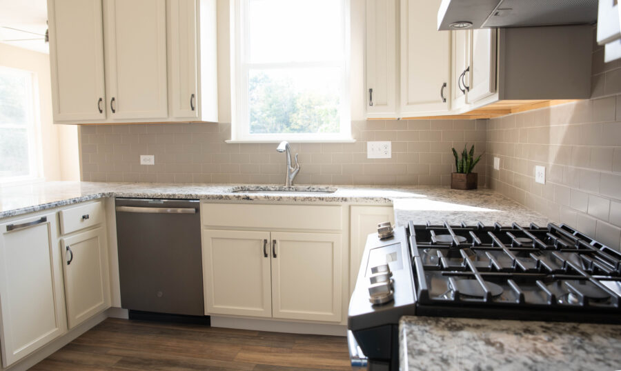 The kitchen' sink wall with subway tile backsplash, the sink below a window, white cabinets, and a gas range stove.
