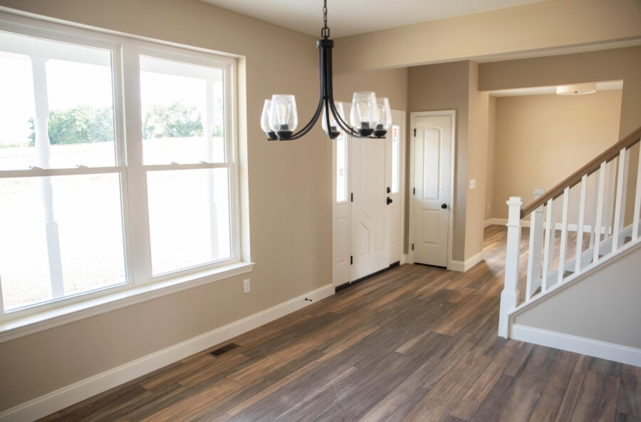 The view from the dining room looking towards foyer with beige walls, a white door, 9' high first floor walls, and a black chandelier and vinyl plank flooring