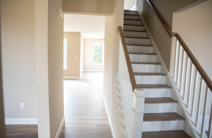 The foyer looking at main stairs up to the 2nd Floor and Great Room with stairs featuring oak stained treads, painted risers with square and painted balusters.