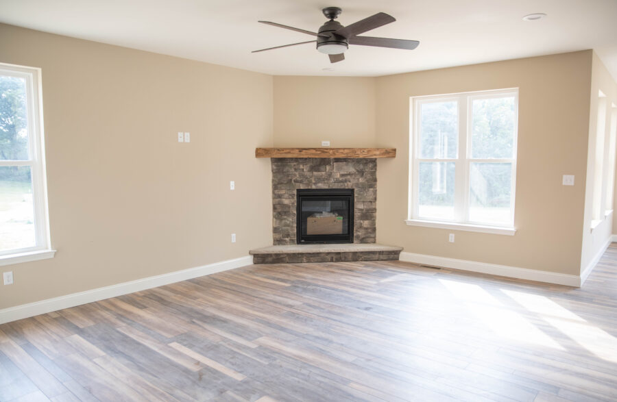 The Great Room with a corner gas fireplace with half height stone surround, a barn beam mantel and a raised hearth with 1-piece stone.
