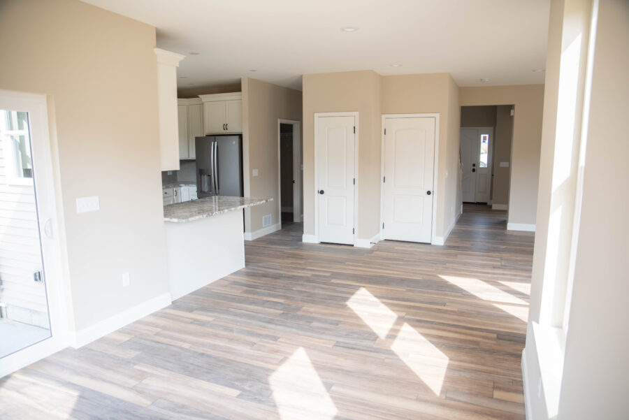 The Breakfast nook looking at kitchen, pantry, and door to basement with tan walls, white doors and trim, and luxury vinyl plank flooring.
