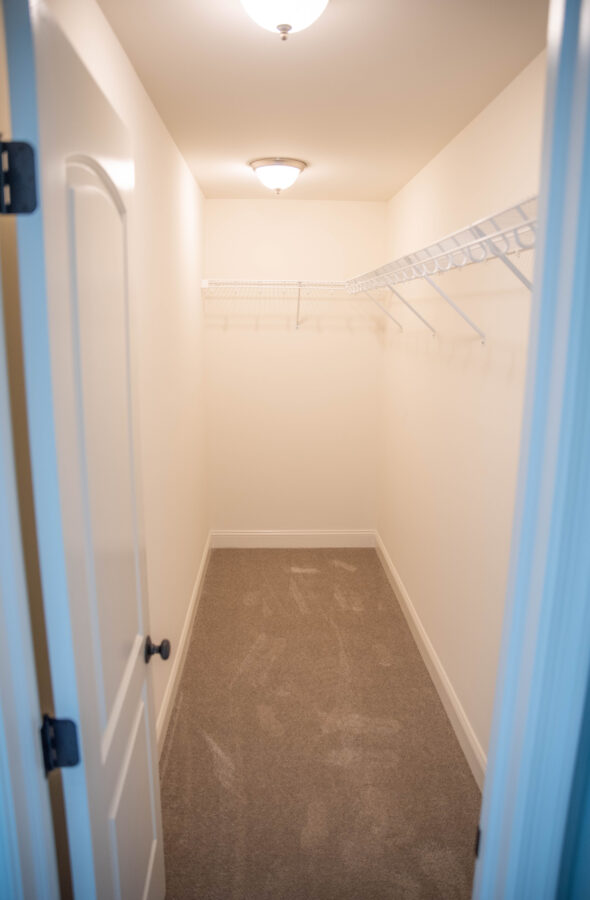 The Master Closet with carpet, white walls and standard free slide wire shelving