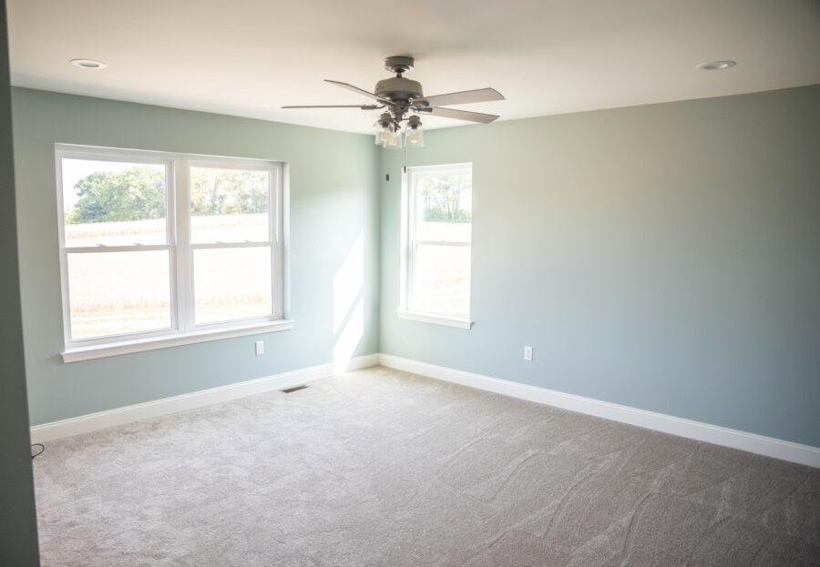 A bedroom with light blue-green walls, windows with white trim, neutral carpet and a ceiling fan.
