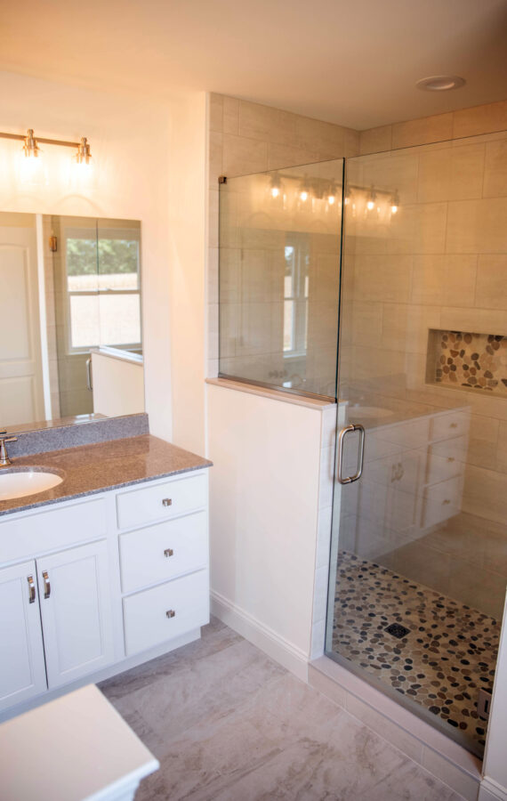 The Master Bathroom with a customized tiled shower with glass door and panel and a white painted vanity with cultured granite countertop.