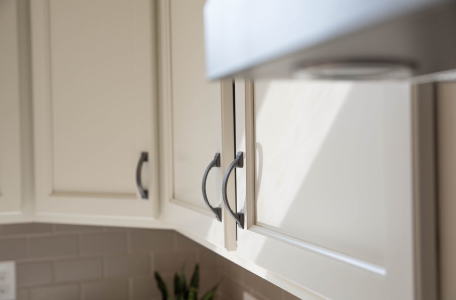 Amerock cabinetry hardware in oil-bronzed finish on white kitchen perimeter cabinets.