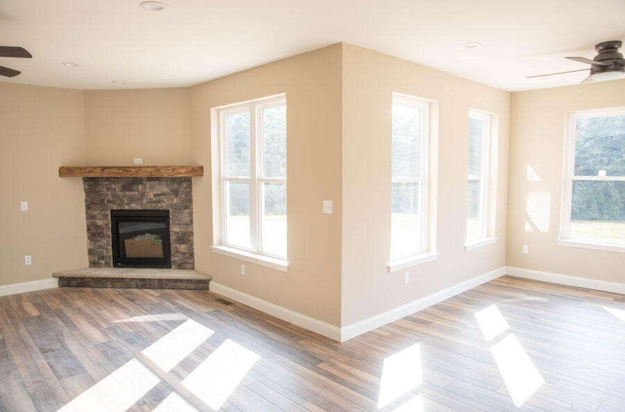 The Great Room and Breakfast Nook with tan walls, white trim, the corner gas fireplace and an open concept living space.
