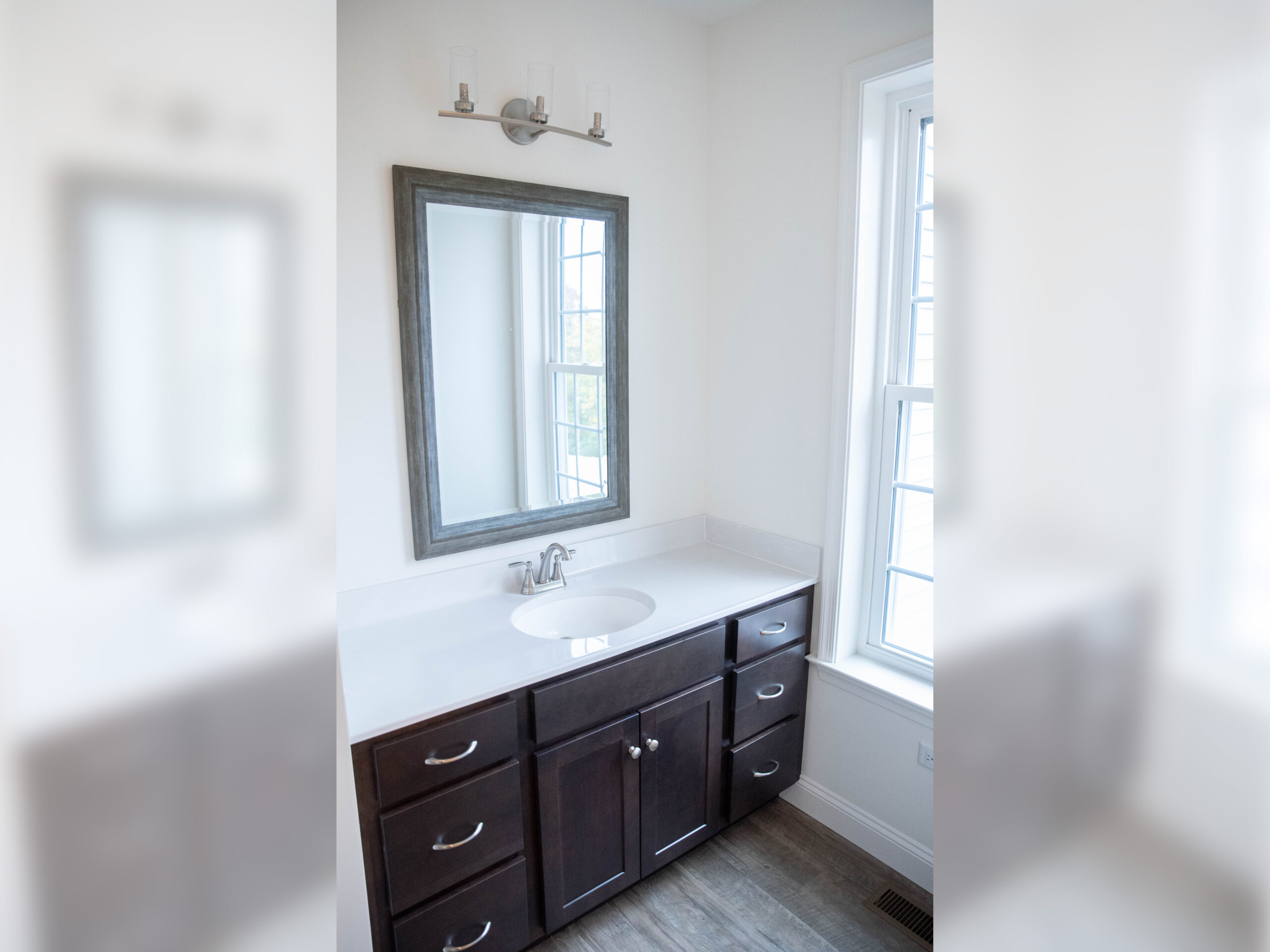 Full bathroom with Cherry stained cabinetry, white cultured marble countertops, white walls and a mirror and vanity lights