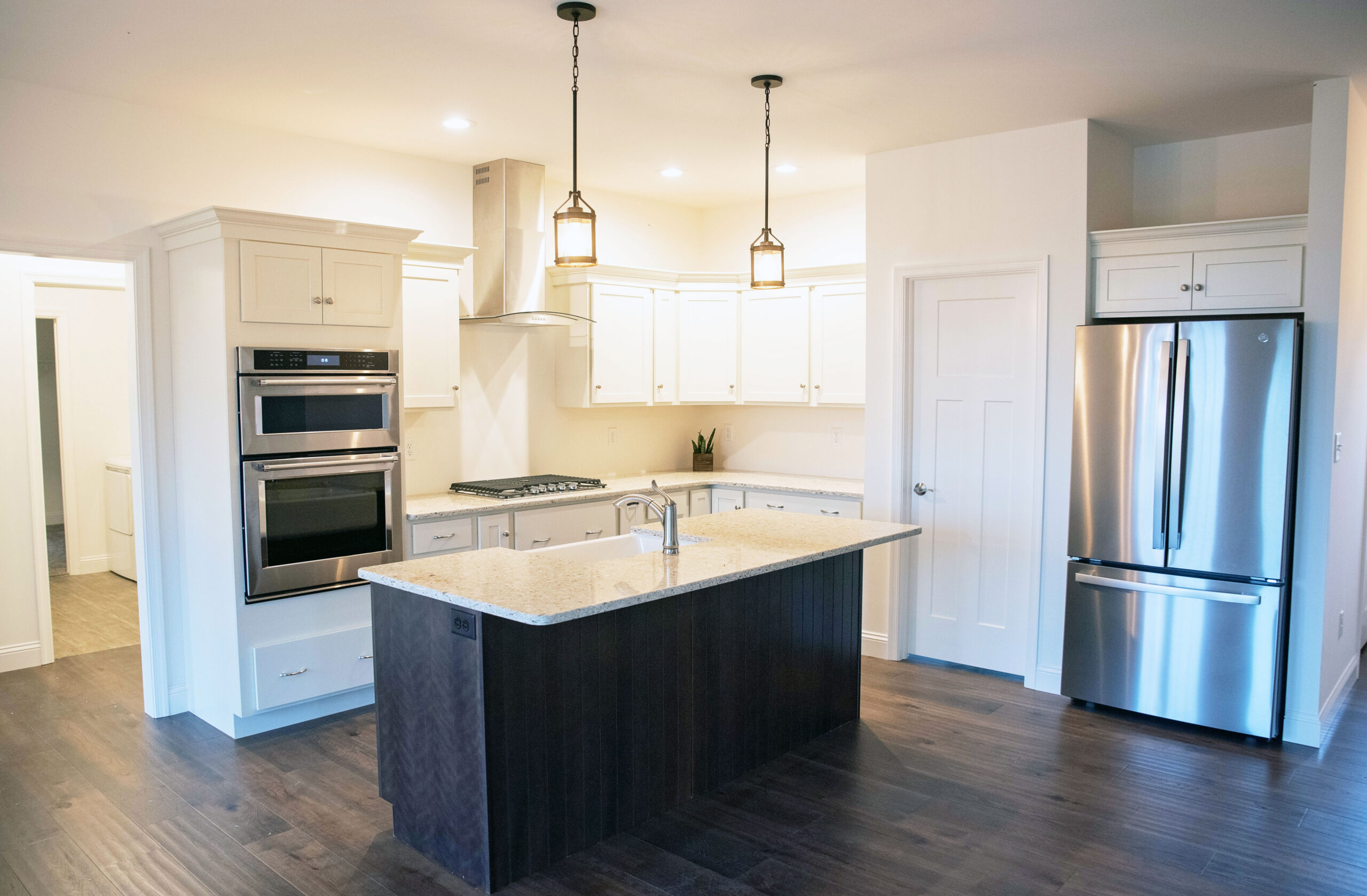 The kitchen with white cabints, a cherry stained island, quartz countertops, and stainless steel appliances.