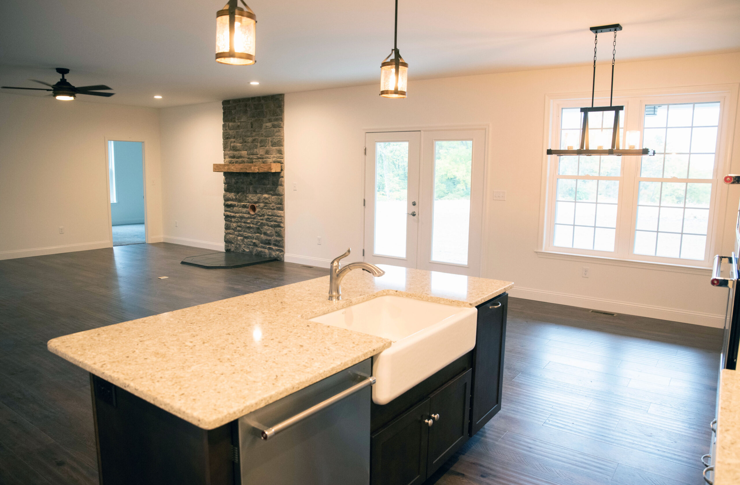 The open-concept Kitchen and farmhouse apron-front sing looking at great room and dining room
