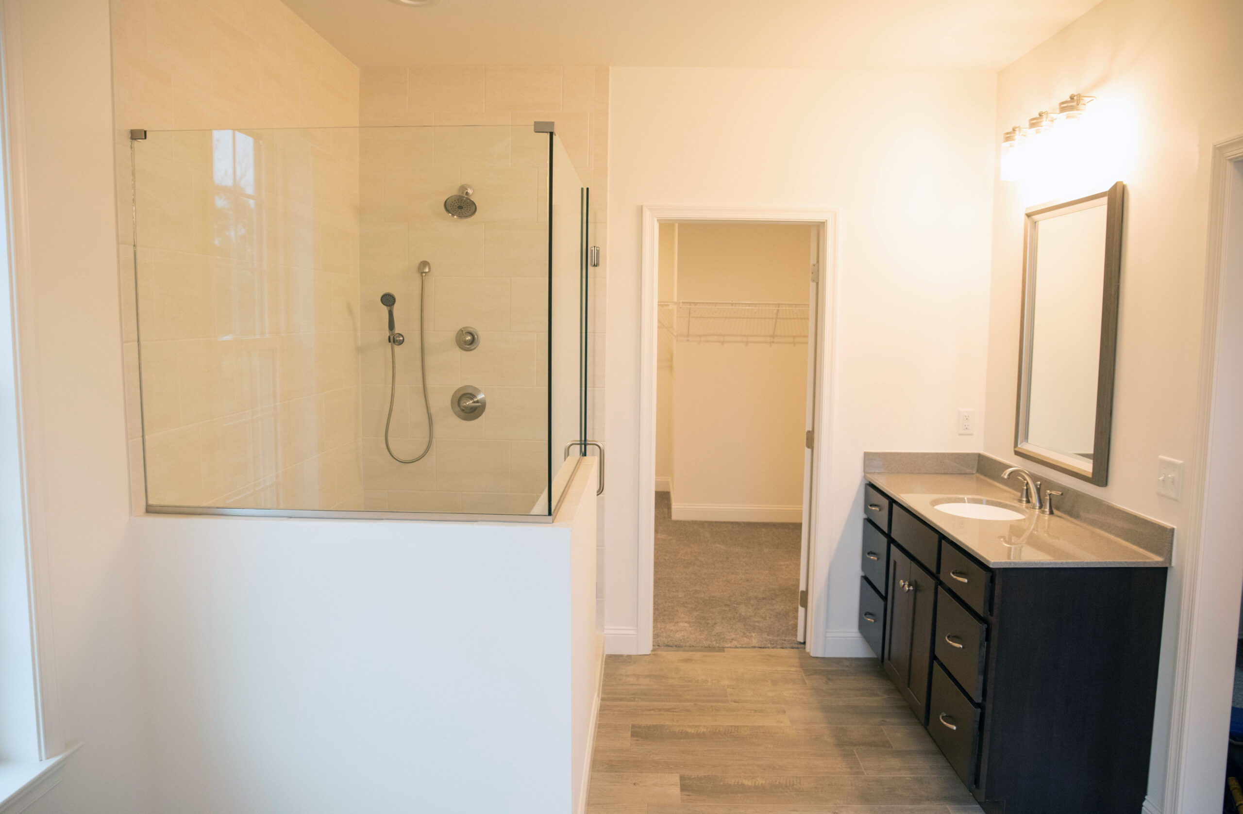 The Master Bathroom has a shower with tiled walls and floor, clear glass swinging shower doors and panels with a vanity and tiled floors.